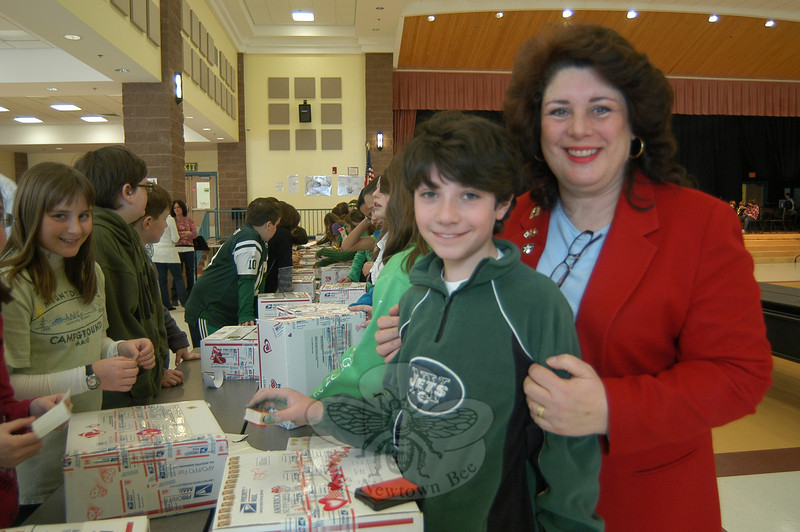 Valentine For Troops project Chair Donna Randle, right, stands with Reed Intermediate School sixth grader Nathan Malota on Friday, January 28, as Reed students packed letters and gathered goods to be sent overseas for troops.  (Hallabeck photo)