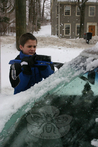 Wednesday morning, Logan Lane was the picture of concentration as he worked to scrape the ice off the windshield of his mom's car.  (Hicks photo)