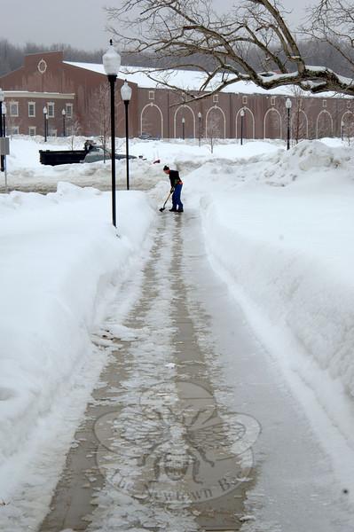Alone on the sidewalk, one man chopped a path along Newtown Municipal Center's sidewalks Wednesday.  (Bobowick photo)