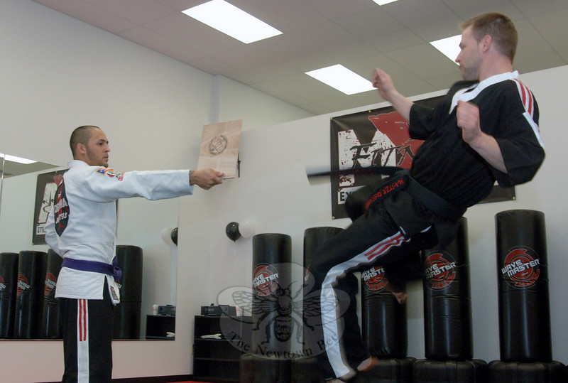 Russ Moore breaks a board held in place by Victor Torres during the February 5 grand opening of Extreme Fitness & Martial Arts, a new business in Plaza South.  (Bobowick photo)