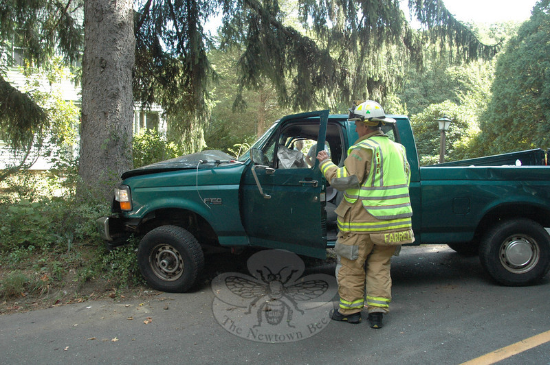 Hawleyville Fire Chief Joe Farrell inspects the driver's compartment of a Ford F-150 pickup truck that crashed into a tree on Farrell Road about 12:19 pm September 16. Police said motorist Jose Minchala, 18, of 29 Old Hawleyville Road was driving the truck northward on Farrell Road, about 250 feet south of its intersection with Patricia Lane, when the truck went off the right road shoulder and then struck a tree. Police said Minchala told them that he was distracted by his dog, which was riding in the truck, before the impact occurred. Minchala reported arm pain and was transported by ambulance volunteers to Danbury Hospital for treatment. Police issued Minchala an infraction for making a restricted turn.  (Voket photo)