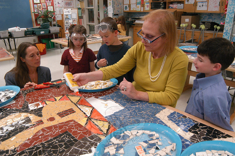 "Art Spot of Danbury co-owner Joanne Hunter showed Sandy Hook School students and Principal Dawn Lafferty Hochsprung, left, how to glue tiles onto an art installation the school is creating with the Art Spot of Pablo Picasso's 1921 ""Three Musicians"" painting on Tuesday, September 21.  (Hallabeck photo)"