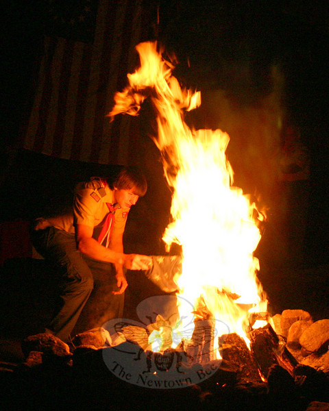 Eagle Scout candidate Michael Hubbard carefully placed an American flag on a fire on Saturday, September 18, during Troop 270's annual flag retirement ceremony. The ceremony was part of the troop's annual campout and Court of Honor, and for the sixth year the boys' families were invited to witness the brief but formal event.  (Hicks photo)