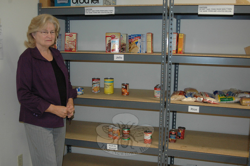 Newtown Social Services Director Ann Piccini stands among the nearly bare shelves at the local Salvation Army food pantry at Town Hall South Tuesday. With donations unusually low this summer, Ms Piccini is hoping for a big turnout of donations to help get needy families through until the holiday season. Food donations will be collected at the Newtown Health Fair Saturday, September 25, at Newtown Middle School.  (Voket photo)