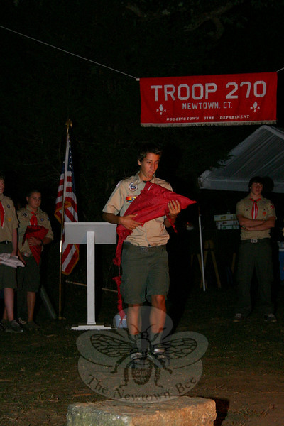 Matt Rosa approaches the campfire with a flag to be retired during a formal ceremony done by Boy Scout Troop 270 last weekend. (Hicks photo)