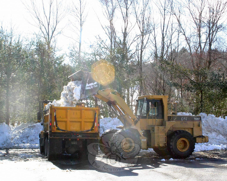 Snow cleanup continued last week, with Parks & Rec crews working with Public Works employees to clear some of the larger piles of snow that remain in parking lots. On February 8, Dan Lewis was running a payloader owned by Nagy Bros, which is among the heavy equipment hired by the town this season to keep up with the weather. Mr Lewis was using the loader in the rear parking lot of C.H. Booth Library, loading full-size dump trucks, including this one being driven by Parks & Rec crew member John Benvenuti.  (Hicks photo)