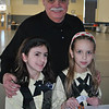 Monsignor Robert Weiss pauses on Friday, February 11, to thank St Rose first grade students Kayla Ondy, left, and Barbie Urban, who were attaching stickers to mailing boxes as part of Valentines For Troops. St Rose students filled 18 boxes with 455 valentines, toiletries, T-shirts, candy, gum, and other small items to send to troops overseas. The students even included dog treats for the service dogs in the boxes of gifts.  (Crevier photo)