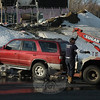 A wrecker operator from Sugar Hill Automotive Service Center attaches an SUV to a wrecker following a one-vehicle rollover accident that occurred on Mile Hill Road about 3:23 pm February 14. Police said that motorist Brandon Body, 17, of 11 Sugar Street was driving a 1998 Toyota 4-Runner SUV southward on South Main Street and then turned left onto eastbound Mile Hill Road. Body lost control of the SUV on the wet pavement and the vehicle then crossed into the westbound lane, after which it struck a snowbank and rolled over. Neither Body nor 16-year-old passenger Justin Brophy of 20 Boggs Hill Road were injured. Ambulance volunteers and Hook & Ladder firefighters responded to the accident. Police said they issued Body an infraction for traveling unreasonably fast. (Gorosko photo)