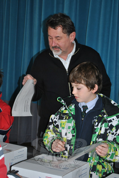 Hawleyville Post Master Mark Favale assists St Rose fourth grade student Mark Leonardi in applying a customs envelope to one for the 18 boxes of valentines the children mailed to troops overseas.  (Crevier photo)