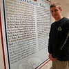 "NHS Junior Sean Decker is shown near his mural, ""Connecticut's Fallen Soldiers,"" in December 2010, as the work was nearing its completion.  (Hallabeck photo)"
