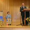 NHS Principal Charles Dumais, at the podium, opened the mural dedication ceremony with brief remarks. Seated on the left is high schol student Taylor Varga, who sang the national anthem Thursday afternoon.  (Hicks photo)