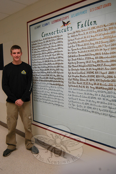 """NHS Junior Sean Decker is shown near his mural, """"Connecticut's Fallen Soldiers,"""" in December 2010, as the work was nearing its completion.  (Hallabeck photo)"""