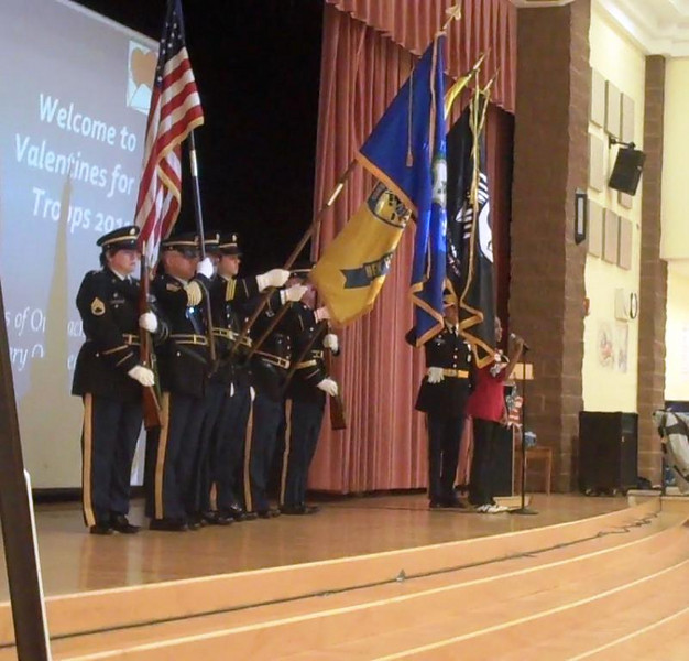 "The Second Company Governor's Horse Guard presented the colors at a ceremony to mark the end of the 2011 effort to send Valentines For Troops on Friday, February 25, while Reed Intermediate School student Olyvia Shaw sang the ""Star Spangled Banner.""  (Hallabeck photo)"