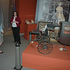 Kathy Maher (left), executive director and curator of The Barnum Museum, chats with an unidentified staff member in front of Tom Thumb's carriage, in one of the museum rooms that bore the brunt of tornadic wind and rain gusts that caused millions of dollars in damage to the Bridgeport site last summer.  (Voket photo)
