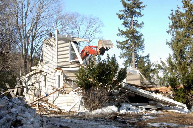 An excavator tears through remaining upright pieces of the state-owned farmhouse at 94 Wasserman Way.  (Bobowick photo)