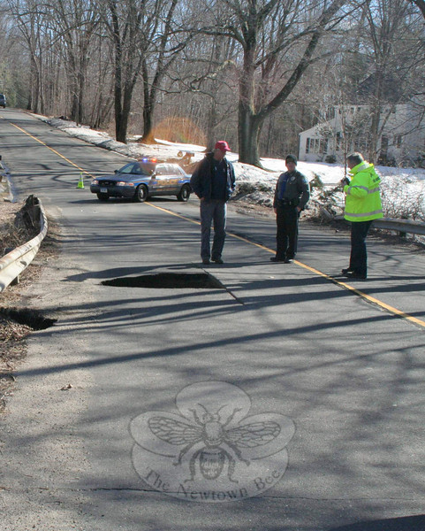 Public Works employees, and Newtown Police Officer Scott Smith, inspect a drainage culvert at Boggs Hill Road near its intersection with Sugar Street early Monday afternoon. A washout created a hole in the roadway that stretched the width of one travel lane. Police temporarily closed off the section of roadway until repairs could be done.  (Hicks photo)
