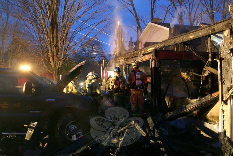 Firefighters stand amid the fire debris of a destroyed attached garage for a residence at 39 Riverside Road in Sandy Hook on Thursday morning. All five local volunteer fire companies, plus Southbury firefighters, were called to the scene.  (Hicks photos)