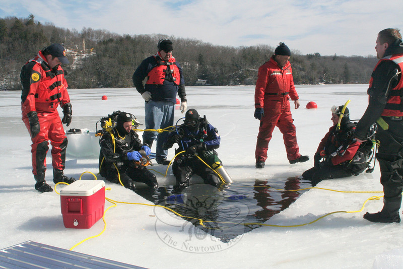 Members of Newtown Underwater Search And Rescue (NUSAR) spent nearly five hours at Eichler's Cove on February 25, training for the possibility of a recovery or rescue in icy conditions. Three of the team's members — Fred LeMay, Jeremy Stein, and Dan Tuck — became certified during Saturday's ice dive certification class, while other members were able to get more time in the water. Standing on the ice, from left, are John Almstead, Rich Rosini, NUSAR Chief Mike McCarthy, and Lieutenant Brian Solt. Seated, having just emerged from the 36 degree water, also from left, are Mr Stein, Mr Tuck and instructor Peter Hearn.  (Hicks photo)