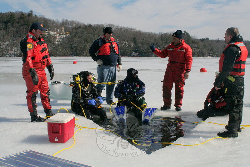 Members of Newtown Underwater Search And Rescue (NUSAR) spent nearly five hours at Eichler's Cove on February 25, training for the possibility of a recovery or rescue in icy conditions. Three of the team's members — Fred LeMay, Jeremy Stein, and Dan Tuck — became certified during Saturday's ice dive certification class, while other members were able to get more time in the water. Standing on the ice, from left, are John Almstead, Rich Rosini, NUSAR Chief Mike McCarthy, and Lieutenant Brian Solt. Seated, having just emerged from the 36 degree water, also from left, are Mr Stein, Mr Tuck and (partially hidden) instructor Peter Hearn.  (Hicks photo)