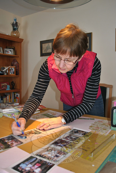 Fran Ashbolt uses a stylus to carefully break the seal around photographs laid out on an adhesive sheet. The pictures can then be placed securely on the album page. Using a repositionable adhesive allows the scrapbooker to move the photos around for an extended period of time.  (Crevier photo)