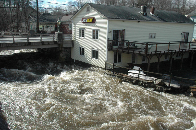 The Pootatuck River nearly went over the six foot-plus stone walls in Sandy Hook Center by late Monday morning.  (Voket photo)