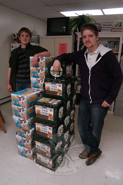 Newtown High School student Charlie Pryor, left, and Doug Pierce raised money and collected dog and cat food to donate to Social Services. The food was donated on Wednesday, March 2.  (Hallabeck photo)