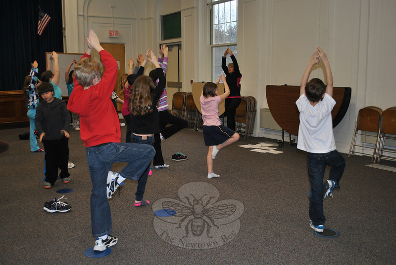 Fourth grade classes of Lea Attanasio and Melissa Thorpe, under the direction of Hawley math and science specialist Deb Cowder, strike a tree pose during a brief yoga session, Friday morning.  (Crevier photo)