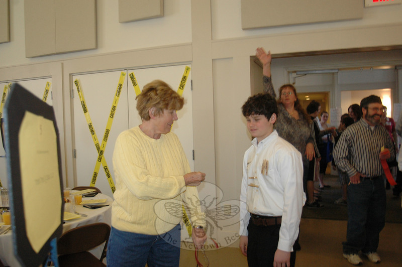 """Connor Hanley, a Newtown High School freshman, had just pinned a """"hug"""" on his grandmother Heidi Mang at the 2011 Workcamp fundraiser and breakfast. Connor's hugs were fashioned out of clothespins that he could clip to various attendees so they could stick with the recipients while he travels to West Virginia on the summer Newtown Ecumenical Workcamp Students (NEWS) journey to help Appalachian families on a human services mission this summer."""