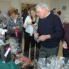 "Al Cramer, center, chooses from among a raft of donated raffle prizes to benefit the 2011 Newtown Ecumenical Workcamp Students (NEWS) project. A fundraising breakfast with entertainment and raffles was held at Newtown Congregational Church on April 2, where neatly attired young work campers served tables full of invited family and friends for ""tips"" that will also help support the group's trip to Brenton, W.Va., this summer.  (Voket photo)"