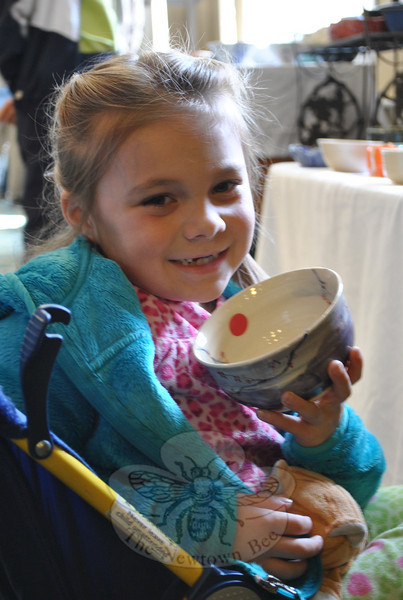 Seven-year-old Juliette Despirito had a broken foot that put her in a stroller, but she was all smiles as she picked out a bowl at Maplewood Spring Fest.  (Crevier photo)