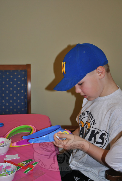 Doug Carriero, 10, embellishes a plastic visor at the craft table during Spring Fest, April 2 at Maplewood.  (Crevier photo)