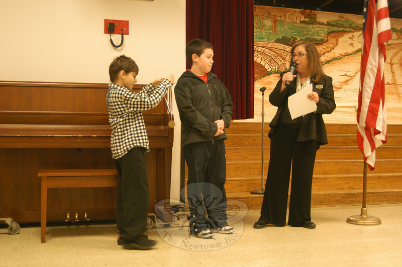 Head O' Meadow students who earned awards in the PTA's Reflections program at the school this year were recognized during a school assembly on Thursday, March 31. Head O' Meadow Principal Barbara Gasparine, right, and student Assistant Principal For the Day Miles Ball, left, handed out medals to each of the winners, like Carter McCleary, center, who earned the Intermediate Photography award and will have his photo sent on to the national level of the PTA competition. Other award recipients named during Thursday's assembly were Kendall Reed and Derek Sieber for their visual arts entries; Madeline Patrick for her photography entry; Lara Wong for her literature entry; and Annie Fowler for her music entry.  (Hallabeck photo)