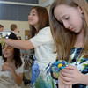 Rebecca Townsend adjusts the ribbons in her corsage, while friends show off their rose petal arrangements in the background during a Confirmation ceremony at St Rose of Lima Church on April 15.  (Bobowick photo)