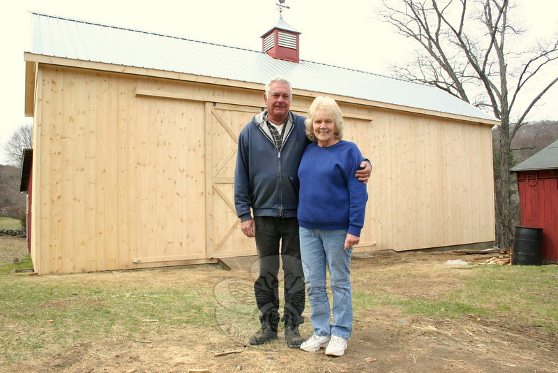Bob and Joyce Staudinger stand in front of the barn that was recently rebuilt at their Pole Bridge Road property. The Staudingers were among the two dozen-plus residents and businesses who were affected this past winter when snow and ice accumulations caused roofs and buildings to collapse. The barn behind them has a 100-year-old foundation and an addition that dates back 50 years, but the main section of the barn had to be rebuilt. A crew from Pennsylvania spent four and a half days in Sandy Hook and, working with Mr Staudinger and son-in-law John Ferris, created a gorgeous new building for the couple's hay harvests.  (Hicks photo)