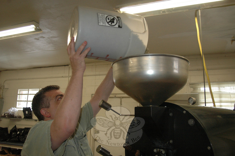At the beginning of a roughly 20-30-minute process, Redding Roasters owner Bill O'Keefe pours the raw coffee beans into a huge roaster. Once he determines by sight, and the sound they make while churning inside the device, that the beans are ready, he will dump, cool, and bag them for his retail and limited number of wholesale customers.  (Voket photo)