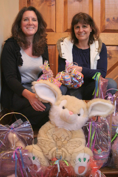 Cyndy DaSilva, left, and Mandy Monaco took a moment following the annual Easter Basket Assembly Brunch Party at Mrs Monaco's home last Friday morning, where in just a few hours they and other members of Women Involved in Newtown (WIN) assembled 150 Easter baskets and 30 bags of candy. As they were being finished on April 15, the collections were immediately taken off to any of four destinations. Newtown Social Services received 82 Easter baskets; Healing Hearts in Danbury received 33, plus the 30 bags of candy for teen-agers who did not want a full basket; Harmony House in Danbury received ten baskets, and AIDS Interfaith Ministry, also in Danbury, received 25. WIN buys the candy for the baskets and is able to send out so many baskets thanks to donations of filler grass and gently used stuffed animals from scout troops, schools and residents.  (Hicks photo)