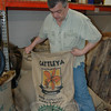 Bill O'Keefe, founder of Redding Roasters, wrestles with a half-full bag of imported coffee beans weighing upwards of 100 pounds at his retail roasting business on Greenwood Avenue in neighboring Bethel. The taupe-colored beans will be roasted into one of numerous varieties of beans or ground coffee that he sells direct to consumers.  (Voket photo)