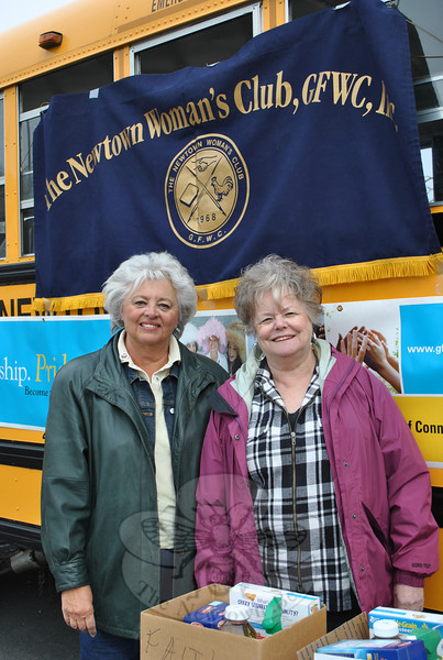 """JoAnn Bruno, left, and Yvonne Kopins of the Newtown Woman's Club, GFWC, Inc, stand in front of Bus 13, owned by Phil Carroll, Saturday morning, April 16, collecting food for the club's fifth annual """"Stuff A Bus"""" food drive to support the Newtown Social Services Salvation Army Food Cupboard at 3 Main Street, and FAITH Food Pantry, located at St John's Episcopal Church in Sandy Hook. The bus, donated for the day by Mr Carroll, was parked in the lot of the Stop & Shop at Sand Hill Plaza, and despite the chilly and rainy day, shoppers donated generously to the cause.  (Crevier photo)"""
