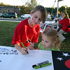 Newtown hosted its first full Light The Night event, a fundraiser for The Leukemia & Lym-phoma Society, on Saturday, September 25. The event took place on the grounds in front of Newtown Youth Academy and included live music, refreshments, LLS and related informa-tion, and a two-lap walk.  Kayla Pettit (left) and Gianna Dimezza were two of the attendees who responded to an invitation by volunteers to sign a banner for future events.  (Hicks photo)
