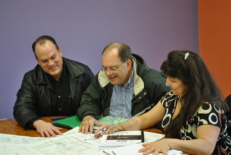 From left is Reverend Matthew Crebbin, the senior minister at Newtown Congregational Church, Ron Galati of Practical Energy Solutions, and Sarah Bollinger of Automated Logic, looking over plans for the heating and cooling systems at the 14 West Street church, Wednesday afternoon, April 20.  (Crevier photo)