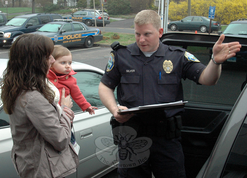 During a review of a car seat inspection with Newtown tax office staffer Cayenne Spremullo and daughter Lia James, local traffic unit officer Jeffrey Silver explained that rear-facing child safety seats do a better job of supporting the head, neck, and spine of infants and toddlers in the event of a crash, because the force of the collision is distributed over the entire body.  (Voket photo)