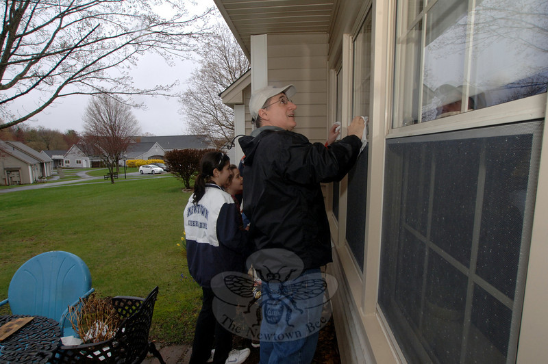 Tim O'Neil cleans the higher windows that the girls, Ashley and Amanda Solomon, cannot reach during the annual Newtown Youth & Family Services Independent Living Day. Residents helped fellow residents at Nunnawauk Meadows on April 23, with light work that brightened their homes and property following winter.  (Bobowick photo)