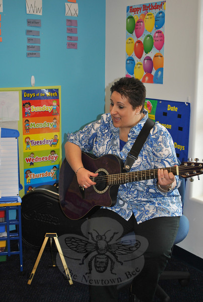 "Janine La Mendola, ""Ms Janine,"" provided guitar music and sign language fun for children at the Learning Experience child care center open house, Saturday, April 16. The open house introduced visitors to the center's upcoming summer camp programs, as well as the new full and half-day kindergarten program starting in September. Open house guests also had a chance to win a raffle basket made up by neighboring business, Good Ideas, a Parent Teacher Store. The Learning Experience is located in Plaza South on South Main Street.  (Crevier photo)"