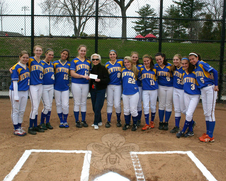 Six months of fundraising efforts were celebrated on April 18 when the Newtown High School Softball Team made a $500 donation to FAITH Food Pantry. From left are team members Courtney Escoda, Nora Murphy, Monica Macchiarulo, Captains Natalie Dunn and Colleen Cunningham, food pantry volunteer Barbara Lynch, Captain Megan Gibbons, and teammates Mady Hauck, Morgan Macchiarulo, Karlie Kuligowski, Danielle Shine, Jessica Gibbons, Abigail Kuligowski, and Kayla O'Grady. Pitcher Emma Herring was unavailable for the photo, but she did help the team later in its 6-3 win over Brookfield.  (Hicks photo)