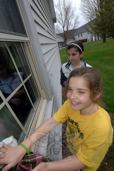 Ashley Solomon, 9, and her sister Amanda, 11, clear winter's film and grit from the windows at Nunnawauk Meadows on Saturday, April 23, as part of an Independent Living Day initiative through Newtown Youth and Family Services.  (Bobowick photo)