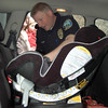 Newtown Police Officer and car seat safety specialist Jeffrey Silver inspects a rear-facing installation for town employee Cayenne Spremullo, as she and her 10-month-old daughter Lia James watch. The American Academy of Pediatrics and the National Highway Traffic Safety Administration issued separate reports recently saying children should ride in rear-facing car seats longer, until they are 2 years old instead of 1.  (Voket photo)