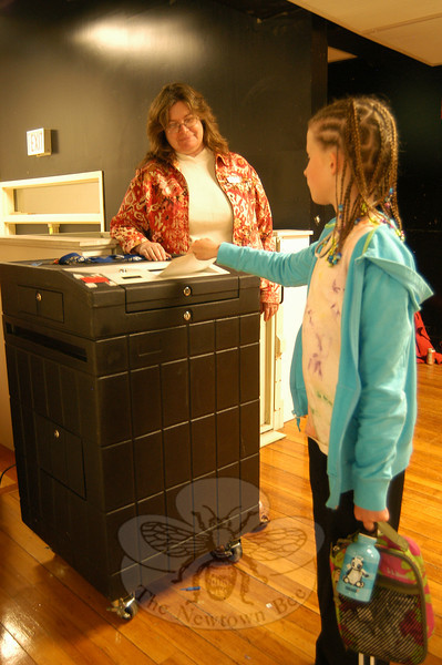 """Head O' Meadow fourth grader Kiera Sughrue, right, turns in her ballot for the school's """"Vote for Books"""" campaign on Monday, April 25, under the guidance of Newtown Democratic Registrar of Voters LeReine Frampton.  (Hallabeck photo)"""