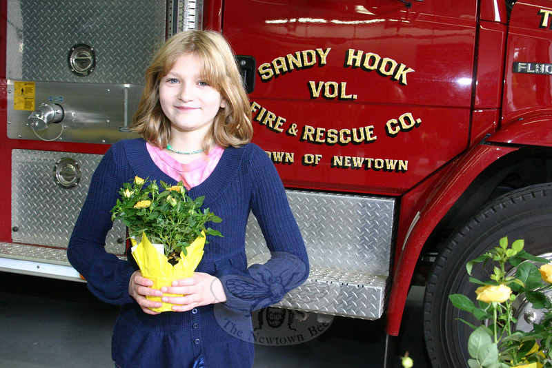 Stephanie Stoyak shows off a small pot of miniature roses, her favorite selection during last weekend's Sandy Hook Fire & Rescue Ladies Auxiliary Flower Sale. Stephanie — whose mom is in the auxiliary and whose dad is the 1st Assistant Chief for the volunteer fire company — was helping during the first day of their annual event, which began on Friday, April 22, and continued to a very successful end by late afternoon the following day. Potted plants, hanging baskets and flats and packs of annuals were all offered. If you missed this event, the women will be offering their second annual event — a Mother's Day Plant Sale with similar items — on Friday and Saturday, May 7-8.  (Hicks photo)