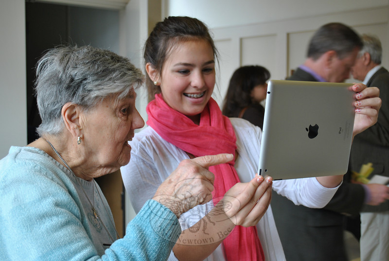 Haley Trudell, a member of Newtown Congregational Church, shows Ilse Foster, 87, how to use the built-in camera on the iPad 2, after church on Sunday, April 17. Ms Foster won the personal tablet computer at a work camp breakfast raffle, April 2, and has enlisted help of friends and family in learning how to use it.  (Crevier photo)