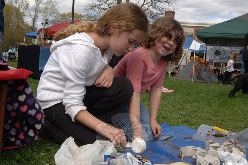 Amanda Carter, left, and Diana Wipf plant wildflower seeds in small containers during the fourth annual Newtown Earth Day Festival on April 30.  (Bobowick photo)